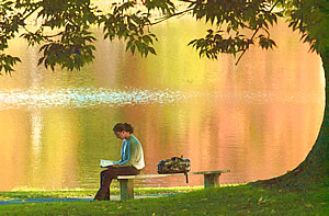 Girl reading by a summertime lake